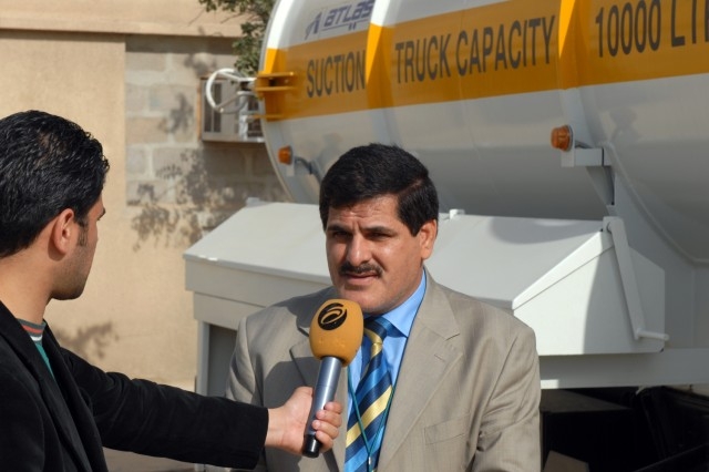 BAGHDAD -A local district leader from eastern Baghdad answers questions from the Iraqi media about 20 waste sanitation trucks turned over to the Government of Iraq during a ceremony at Forward Operating Base Loyalty, Iraq, Feb. 25.