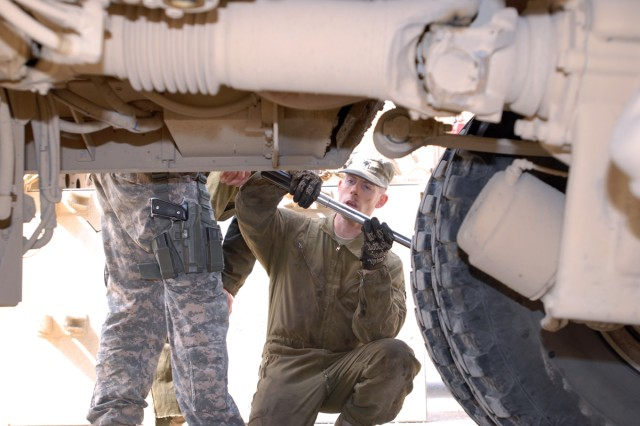BAGHDAD - Spc. Thomas Parker, a light-wheeled vehicle mechanic from Salem, Ore., deployed with Headquarters Support Company, Division Special Troops Battalion, 1st Cavalry Division uses a torque wrench to tighten a bolt on a Mine-Resistant Ambush Protected vehicle at Camp Liberty Feb. 26.