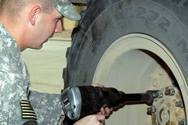 BAGHDAD - Spc. Anthony Theriot, a tactical vehicle operator from Atlanta deployed with D Troop, Division Special Troops Battalion, 1st Cavalry Division, puts a tire back on a Mine-Resistant Ambush Protected vehicle after  completing repairs Feb. 26, at Camp Liberty.