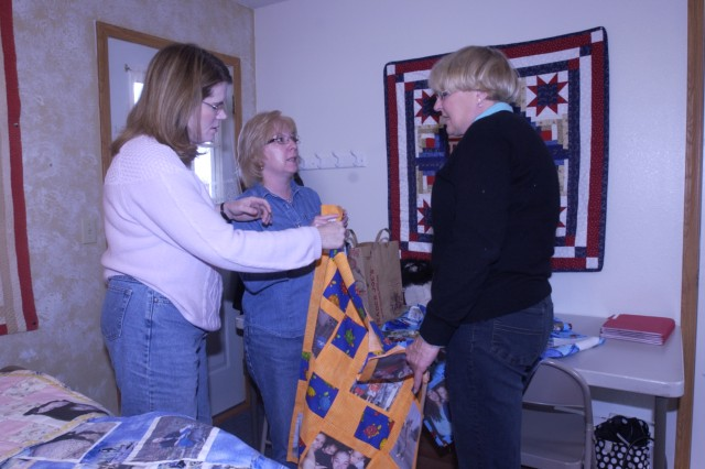 From left, Coleen Twitchell, Carol Tipton and Vicki Whites discuss one of the Operation Kid Comfort quilts at Portia Ellis's home, Feb. 13.