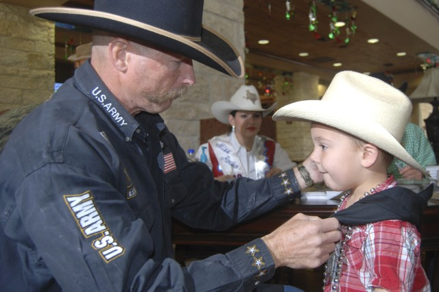 Army Ranger retired Lt. Col. Ron Benton, 5th Recruiting Brigade Contract Cowboy Recruiter, ties a bandana around the neck of young cowboy Gavin Ford. Benton, with San Antonio Stock Show and Rodeo celebrities, visited wounded warriors and their families at the Warrior and Family Support Center Feb. 18.