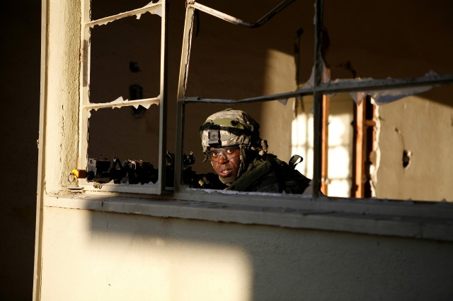 Spc. Janashe Daniel, 3rd Plt., A Co.,  4-23 Inf. provides security as his squad clears a house.