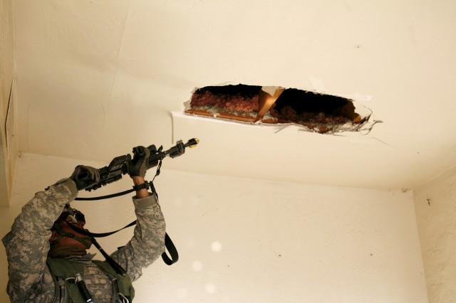 Staff Sgt. Arturo Brito, 3rd Plt., A Co.,  4-23 Inf. scans the ceiling of a house, Feb. 18, during an operation.