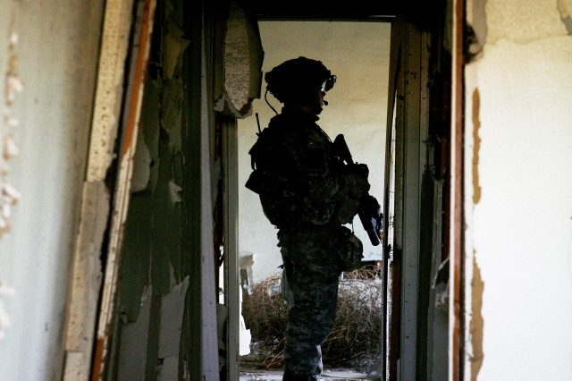 A 4-23 Inf. Soldier stands in the hallway of a cleared house, Feb. 18, during an operation at NTC.