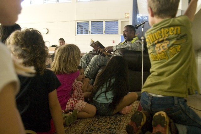 "WHEELER ARMY AIRFIELD, Hawaii - Command Sgt. Maj. Robert Williamson (center), U.S. Army Garrison-Hawaii, reads to a group of children during the ""Tell Me a Story"" event at Wheeler Elementary School, Feb. 11."