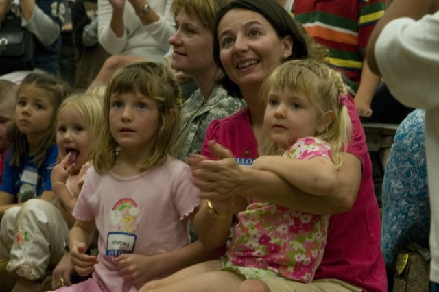 "WHEELER ARMY AIRFIELD, Hawaii - Maj. Kathy Fox (center), Defense Information Systems Agency-Pacific, along with daughters Mackenzie, 5 (left) and Kylie, 3 applauded the end of the story ""More Than Anything Else."" More than 60 families gathered together at Wheeler Elementary School for a night of reading and creative discussion."