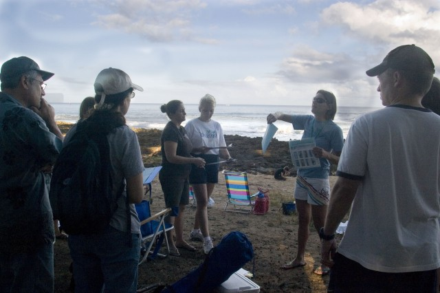 PUAENA POINT BEACH, Hawaii  - Site leader, Renee Bergeron (center), National Oceanic and Atmospheric Administration, explained various whale behaviors and data collecting to volunteers, Jan. 31. Hundreds of volunteers gathered at 56 sites statewide to collect date on the migrating animals.