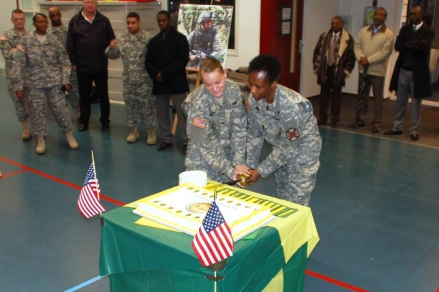 NCO Generations - USAG Schinnen Command Sgt. Major Mary L. Brown (right), the garrisons senior NCO, cuts a cake with the garrisons junior NCO, Sgt. Aunna M. Neuser, at the Year of the NCO kick-off  event in the Activity Center Feb 26, which included presentations of NCO history, the NCO Creed and displays.