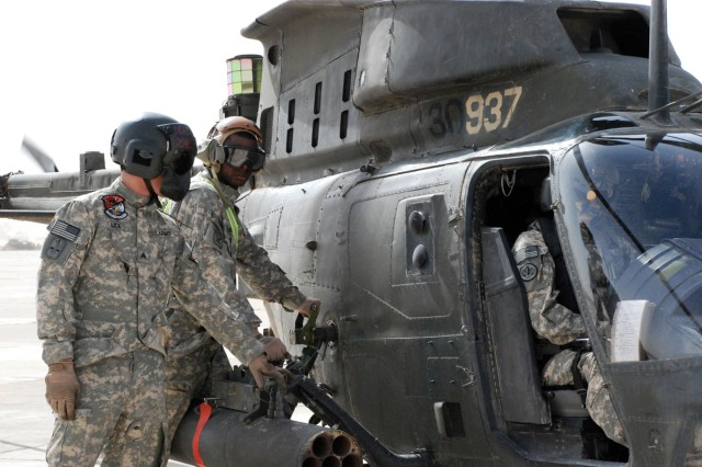 Armament avionics supervisor Sgt. Francis Mix, Delta Troop, 6th Squadron, 6th Cavalry Regiment, 10th Combat Aviation Brigade (left) stands by while Spec. Brandon Martin, Echo Troop, refuels an OH-58D Kiowa Warrior Feb. 21 at the Forward Arming and Refueling Point (FARP) on Forward Operating Base Warrior, Kirkuk.
