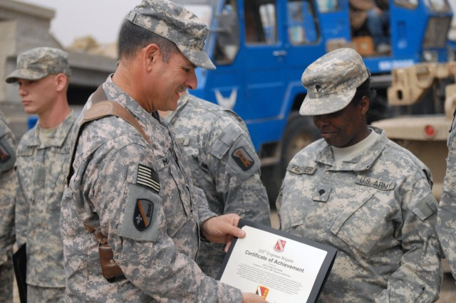 CAMP LIBERTY, Iraq - Gulfport Miss., native Spc. Susie Fautner, a member of Company A, 890th Engineer Battalion, 225th Engineer Brigade, 1st Cavalry Division, Multi-National Division-Baghdad, receives a certificate of achievement from Command Sgt. Maj. Joe Major, of Ventress, La., during an awards ceremony Feb. 27. Fautner received the certificate for his meritorious service and achievements over the last seven months conducting barrier yard operations throughout Baghdad, maintaining over 2,000 barriers on a monthly basis.