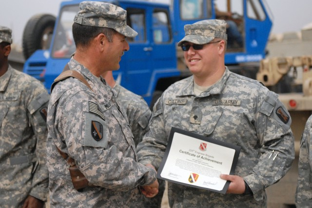 """CAMP LIBERTY, Iraq - Jackson Miss., native Spc. Michael Collins (right), a member of Company A, 890th Engineer Battalion, 225th Engineer Brigade, 1st Cavalry Division, Multi-National Division-Baghdad, receives a certificate of achievement from Command Sgt. Maj. Joe Major, of  Ventress, La., during an awards ceremony Feb. 27. Collins received the certificate for his meritorious service and achievements over the last seven months conducting barrier yard operations throughout Baghdad, maintaining over 2,000 barriers on a monthly basis. """""""
