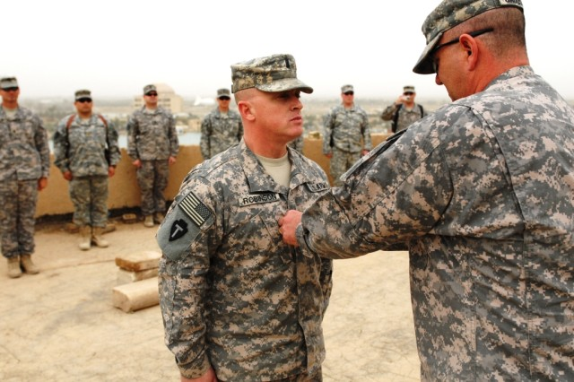 BAGHDAD - Lt. Col. Robert Gaudsmith (right), commander of 1st Squadron 124th Cavalry Regiment, 56th Infantry Brigade Combat Team, Multi-National Division-Baghdad, promotes 1st Lt. John Robinson, personnel officer for the squadron, to the rank of captain during a ceremony held at Victory Base Complex Feb. 27. Robinson, from Zephyr, Texas, graduated from the University of Texas and received his commission through officer candidate school.