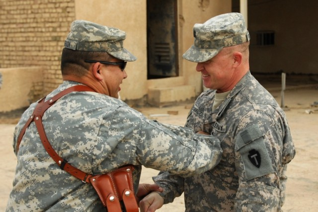 BAGHDAD - Capt. John Robinson (right), personnel officer for 1st Squadron 124th Cavalry Regiment, 56th Infantry Brigade Combat Team, 36th Infantry Division, Multi-National Division-Baghdad, gets a congratulatory tap on the chest from Maj. Timothy Amerson, civil military operations officer for the 56th IBCT, during a promotion ceremony held at Victory Base Complex on Feb 27. Robinson, from Zephyr, Texas, attended officer candidate school to receive his commission and is where he first met Amerson.