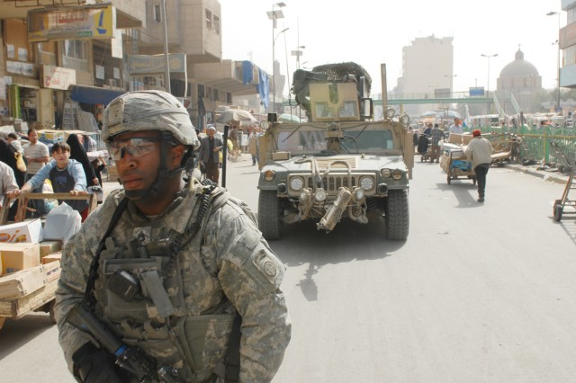 BAGHDAD -Staff Sgt. Daniel Dixon, 5th Squadron, 73rd Cavalry Regiment, 3rd Brigade Combat Team, 82nd Airborne Division, clears the way for his humvee through the open-air Shorja market in Central Baghdad Feb. 26.