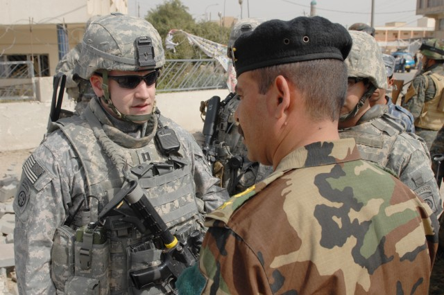 BAGHDAD - Capt. Andy Rohrer, commander, Troop B, 5th Squadron, 73rd Cavalry Regiment, 3rd Brigade Combat Team, 82nd Airborne Division, talks with an Iraqi Army officer, Feb. 26, about a recently detonated improvised explosive device on in Central Baghdad. Rohrer, a native of Grand Rapids, Mich., and his troops support their Iraqi Security Force partners through joint operations.