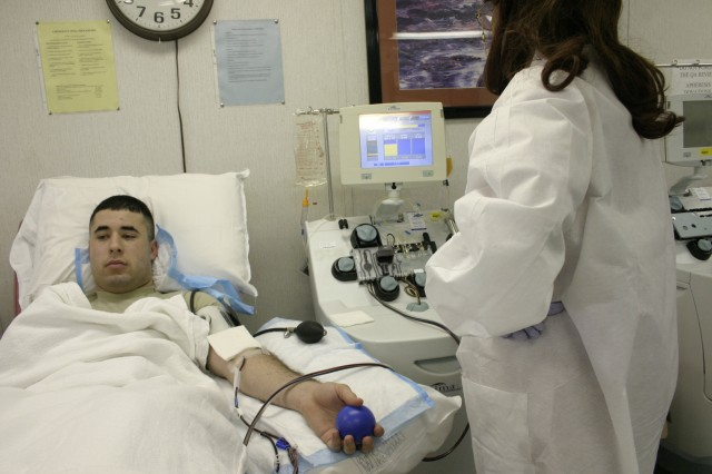 Spc. Christopher Cosio, 3rd Battalion, 82nd Combat Aviation Brigade, 82nd Airborne Division, donates platelets through an apheresis machine while Myra Coston, Fort Bragg Blood Donor Center technician, monitors the apheresis machine. A platelet donation (inset) involves withdrawing whole blood, separating out about 10 percent of the specific platelet cells, and returning the rest of the donor's cells and blood fluids back to the donor's system.