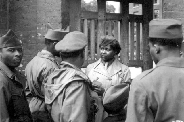 "The first African American Women's Army Corps members to arrive in Europe were 800 women of the 6888th Central Postal Directory Battalion. After the battalion set up its facilities at Rouen, France, it held an ""open house,"" which was attended by  hundreds of African American Soldiers. Pvt. Ruth L. James is on duty at the gate, May 26, 1945."