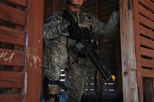 Spc. William Cheatwood of Company B, 2nd Battalion, 325th Airborne Infantry Regiment, 2nd Brigade Combat Team, 82nd Airborne Division, pulls security as fellow paratroopers search through a barn for weapons hidden by a local insurgent force during a situational training exercise at Fort Bragg.
