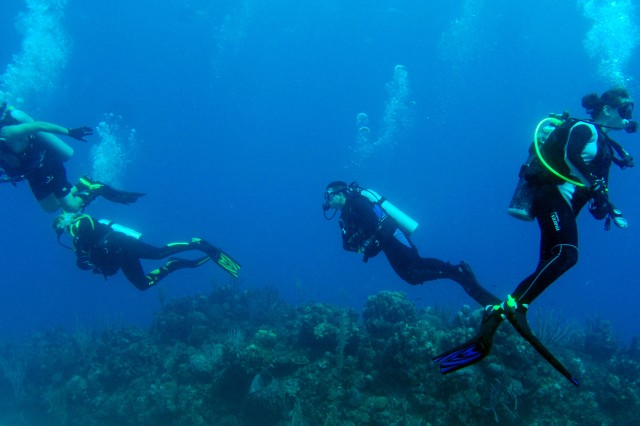 Divers swim over the reef during their certification dives as part of the Soldiers Undertaking Disabled Scuba program. The program teaches disabled and wounded recovering veterans how to scuba dive. Joint Task Force Guantanamo troopers volunteered their time to participate in the SUDS visit.