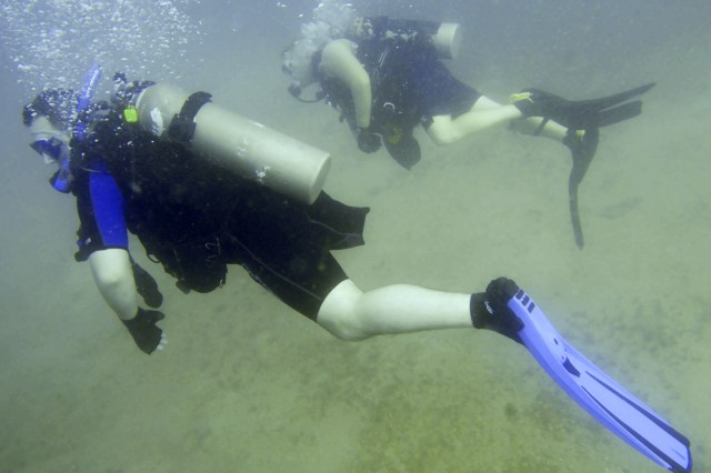 Charles James Shaffer swims through the water during his first certification dive as part of the Soldiers Undertaking Disabled Scuba program, Dec 5, 2008. Several members of Joint Task Force Guantanamo volunteered to assist the program, which teaches recovering disabled and wounded veterans how to scuba dive.