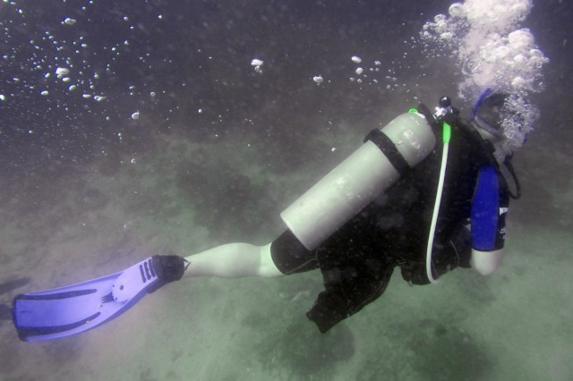Charles James Shaffer swims through Guantanamo Bay during his first certification dive as part of the Soldiers Undertaking Disabled Scuba program. Several members of Joint Task Force Guantanamo volunteered to assist the program, which teaches disabled and wounded recovering veterans how to scuba dive.