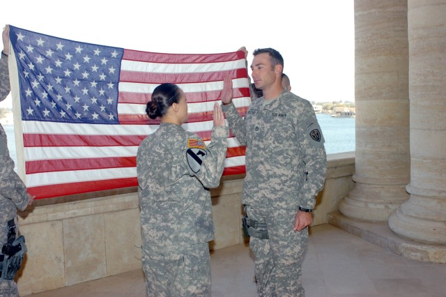 VICTORY BASE COMPLEX, Iraq - Cape Coral, Fla. native Sgt. 1st Class Shane Beckham (right), a military intelligence noncommissioned officer for the 303rd Military Intelligence Battalion, receives the oath of enlistment from his wife, Chief Warrant Officer 2 Chastity Beckham, an imagery technician for the Division Special Troops Battalion, 1st Cavalry Division, Multi-National Division-Baghdad from Oxnard, Calif., at al-Faw Palace March 2 during his reenlistment ceremony. Shane works on Camp Slayer while Chastity works on Camp Liberty. The Beckhams have been married for eight years and previously deployed together to Bosnia.