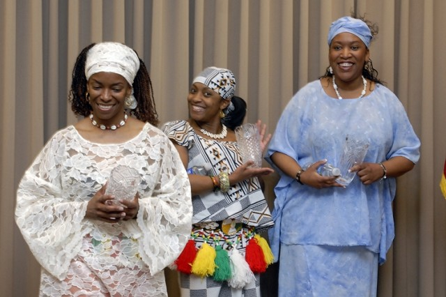 Members of Oluwaseyi, an African folk dancer troupe, receive crystal vases after their performance. Left to right: Jataun Meadows, Angela Boyce, and Lisa Watkins.
