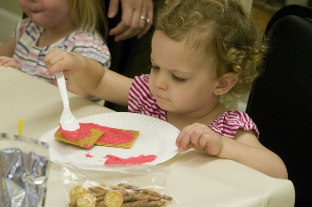 "WHEELER ARMY AIRFIELD, Hawaii - Ava LaMar, 2, spreads red frosting on a graham cracker for the base of her edible fire truck. Fourteen children gathered for the monthly ""Kids in the Kitchen"" event to experiment with food, Feb. 23 at the Armed Services YMCA."