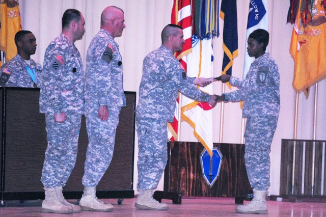 CSM William Ulibarri gives a copy of the NCO Creed to SGT Ritasha Pugh, 1st Battalion, 50th Infantry Regiment, during the Fort Benning Year of the NCO Kickoff Ceremony Tuesday at Marshall Auditorium.