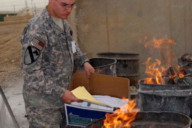 CAMP LIBERTY, Iraq -Spc. Jonathan Fillion, a satellite communications operator maintainer with Company C, Division Special Troops Battalion, 1st Cavalry Division, burns documents in burn barrels.  According to Master Sgt. Mario Dovalina, operational security manager for Multi-National Division-Baghdad, shredding documents is the best method for destroying documents prior to burning them, but burning is fine as long as they are burned thoroughly.