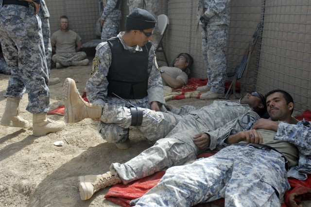 An Iraqi Policeman, from the Muthana Tactical Security Unit in southern Iraq, provides combat casualty care to an American Soldier who is role playing as an injured detainee during a two-week training exercise near Contingency Operating Base Adder, Iraq, Feb. 28. The 2nd Battalion, 12th Cavalry Regiment, 4th Brigade Combat Team, 1st Cavalry Division troops taught the Iraqi Security Forces advanced troop leading procedures and leadership techniques during the two-week training event. ""