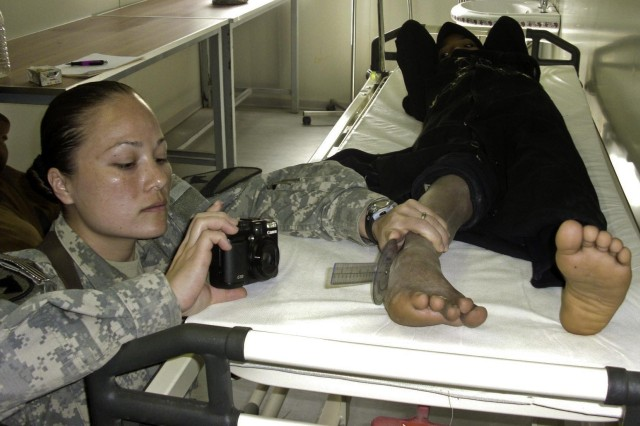 Capt. Candi Darst, a physical therapist, assigned to the 27th Brigade Support Battalion, 4th Brigade Combat Team, 1st Cavalry Division, makes a photographic record of a patient's foot.