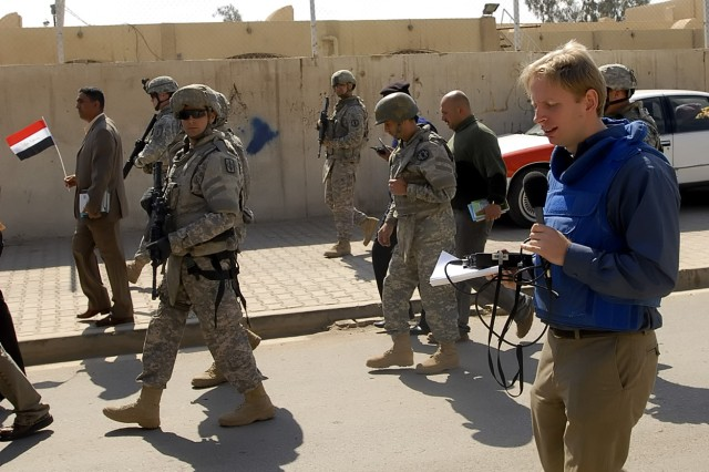 Mike Sergeant (blue vest), of the British Broadcasting Company, speaks into his voice recorder during the Sulla Media Day, March 2, hosted by the 1st Combined Arms Battalion, 18th Infantry Regiment, 2nd Heavy Brigade Combat Team, 1st Infantry Division, Multi-National Division-Baghdad. The event gave both western and Arabic media outlets the opportunity to see progress in northwest Baghdad.