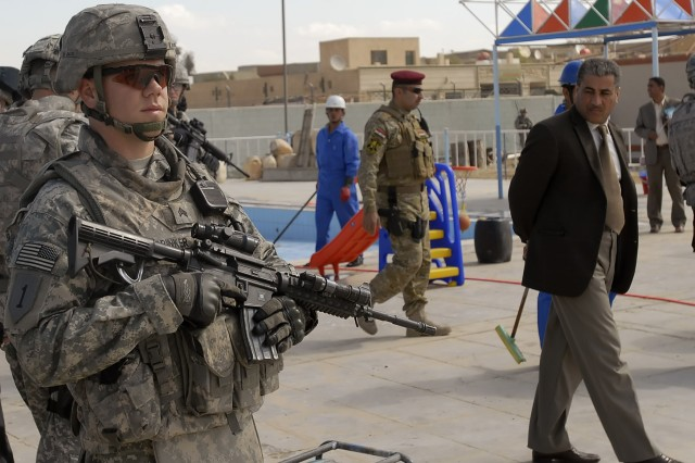 Sgt. Phillip Brinker, 2nd Heavy Brigade Combat Team, 1st Infantry Division, Multi-National Division-Baghdad, waits at a neighborhood swimming pool in northwest Baghdad, March 2. Brinker helped escort numerous Arabic and western media agencies around the Shulla area to see structural and economic improvements.