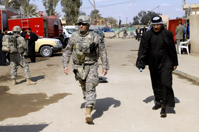 Lt. Col. Philip Smith (left), public affairs officer, Multi-National Division-Baghdad, walks the streets of the Shulla neighborhood of northwest Baghdad during a media walk-through, March 2. Shortly before the walk-through, various Arabic and western media witnessed the transfer ceremony of Joint Security Station Shulla, in which the 1st Combined Arms Battalion, 18th Infantry Regiment, 2nd Heavy Brigade Combat Team, Multi-National Division - Baghdad, handed over the station to the 2nd Battalion, 22nd Brigade, 6th Iraqi Army Division.