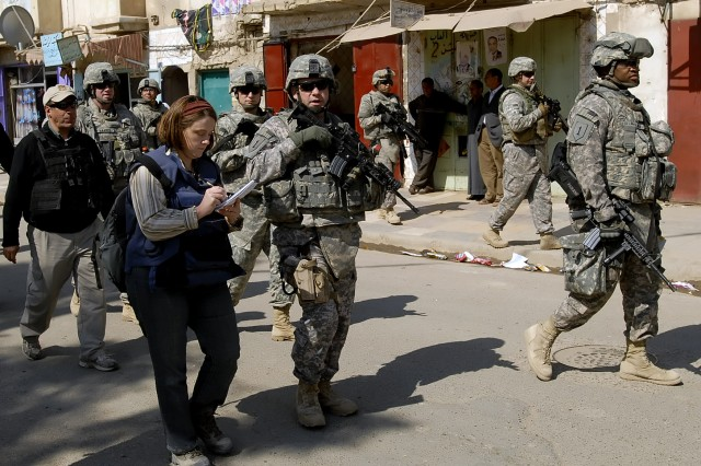 Kim Gamel (left foreground), of the Associated Press, interviews Lt. Col. John Vermeesch, a native of Marshall, Mich., commander, 1st Combined Arms Battalion, 18th Infantry Regiment, 2nd Heavy Brigade Combat Team, 1st Infantry Division, Multi-National Division-Baghdad, March 2 about working with the 6th Iraqi Army Division to secure the population of the Shulla neighborhood of northwest Baghdad in a media walk-through of the neighborhood. Gamel, along with numerous Arabic and western media, also glimpsed a rebuilt and refurbished chicken restaurant, which was heavily damaged in an insurgent attack in late December 2008.