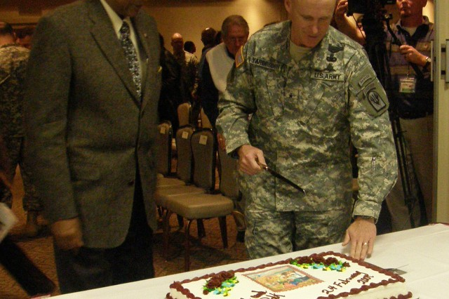 Retired Maj. Gen. Fred A. Gorden, guest speaker at the Black History Month Celebration held at the Warrior Community Center Feb. 24, stands with Brig. Gen. James C. Yarbrough, commanding general, Joint Readiness Training Center and Fort Polk, as they prepare to cut the cake in celebration of the day.