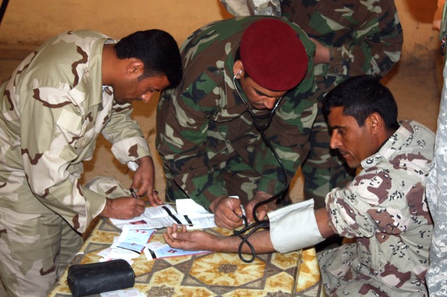 Troops from the 10th Motorized Transportation Unit, 10th Division Iraqi Army check one of their fellow Soldiers for high blood pressure during a health fair at Camp Whitehorse near Contingency Operating Base Adder, Iraq, Feb. 28. The Iraqi led training event consisted of classes that informed the IA's on different preventative-medicine techniques that are available in order to stay physically fit and healthy.