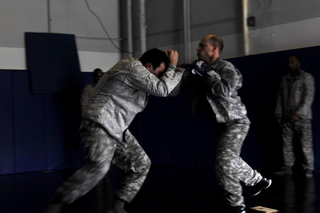 """Staff Sgt. Michael Zuk (left) takes on """"puncher"""" Staff Sgt. Joseph Bicchiera, both from the Noncommissoned Officer Academy on Fort Meade, during a Combatives Level 1 Clinch Drill Feb. 27 at the Warrior Combatives Facility."""