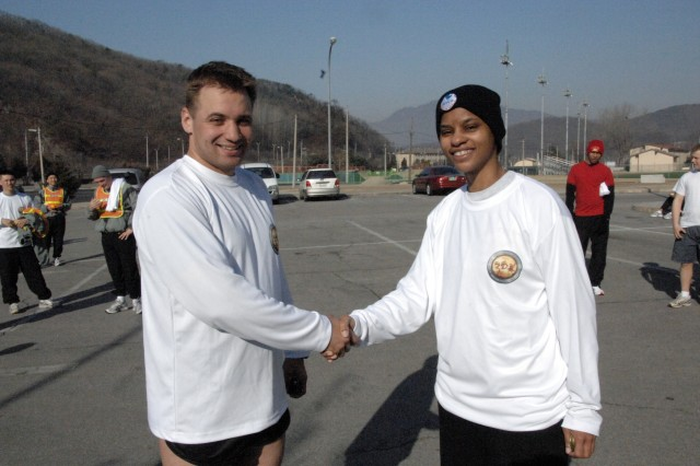 John Hamilton (left) receives a coin from Command Sgt. Maj. Earlene Lavendar (right), USAG-RC Command Sgt. Maj., after finishing 1 with a time of 18:58:23 in the Year of the NCO 5k Fun Run held in front of the Carey Fitness Center on USAG-Casey Feb. 28. - U.S. Army photo by Jim Cunningham