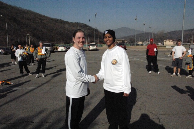 Virginia Metzger (left) accepts coin from Command Sgt. Maj. Earlene Lavendar, USAG-RC Command Sgt. Maj., for finishing 1 in the Women's Division with a time of 19:40:14 during the Year of the NCO 5k Fun Run held on USAG-Casey Feb. 28. - U.S. Army photo by Jim Cunningham