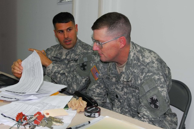 2nd Lt. Joseph Macchariarella, 8th Special Troops Battalion Adjutant, left, briefs Lt. Col. Edward Burke, 8th STB Commander, on the current personnel status of 8th Theater Sustainment Command Soldiers, Mar. 3, at the forward command post on Camp Zama, Japan.