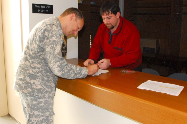 Maj. Tom McCort, 8th Theater Sustainment Command (TSC) deputy chaplain, signs for his security badge from Judd Tritt, 8th TSC security specialist, Mar. 4.  More than 150 Soldiers from the 8th TSC and other units converged on Camp Zama, Japan for a command post exercise.