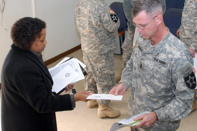 Gwendolyn McCarthy, Army Emergency Relief officer, passes out additional information about the AER to a unit representative at the AER campaign kickoff meeting in the USAG-Casey mini theatre, Feb. 25. - U.S. Army photo by Pvt. Jamal Walker