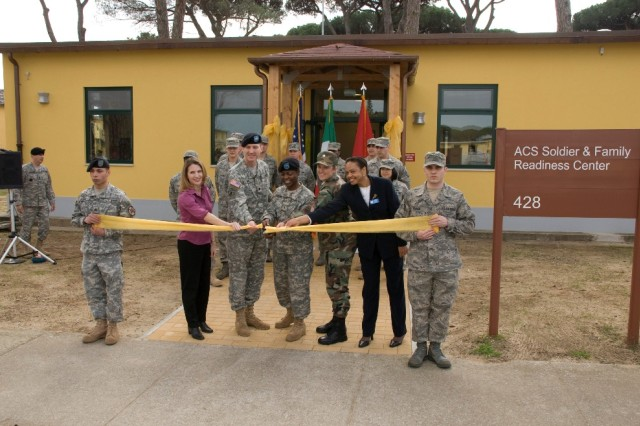 Army Sgt. Chris Everett and Air Force Senior Airman Poirier hold the yellow ribbon as Rebecca Cade (left); Lt. Col. Steve Cade, U.S. Army Garrison Livorno commander; Brig. Gen. Belinda Pinckney, director of the Army Diversity Task Force; Lt.Col. Tammy Cobb, 31st Munitions Squadron commander; and Evelyn Watkins, Army Community Service division chief, officially open Camp Darby's Servicemember and Family Readiness Center in Italy.