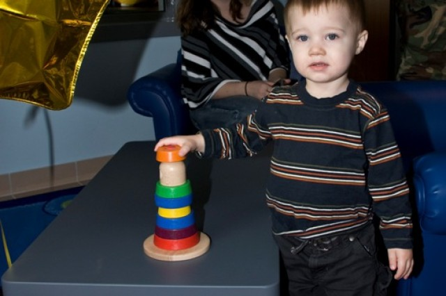 A young child decides to test out the new toys in the children's playroom in the new Camp Darby Servicemember and Family Readiness Center in Italy. The room has video monitoring and large windows so children can play while parents talk to their deployed spouses in a tech room.