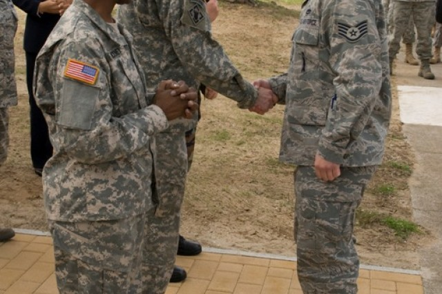 Brig. Gen. Belinda Pinckney, director of the Army Diversity Task Force, and Lt. Col. Steve Cade, commander of U.S. Army Garrison Livorno, Italy, welcome a recently redeployed Airman at the garrison's Family Readiness Center grand opening ceremony Feb. 27.