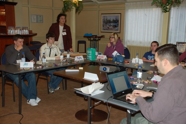 "The Teen Army Family Action Plan Work Group for U.S. Army Garrison Schinnen, the Netherlands, suggested that military ID cards reflect ""student"" on the face of the cards, enabling teens to take advantage of student discounts and other benefits available only to them. Members of the group are shown here with Schinnen's workforce development specialist Kathy Foley."