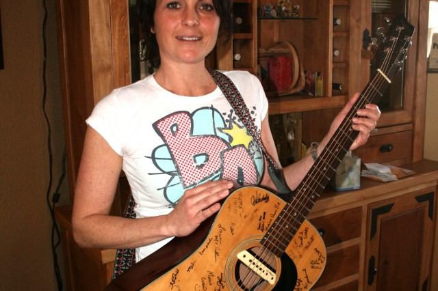 FORT CARSON, Colo.-Amy Downing shows off her guitar at her home Feb. 26. The guitar has been signed other Family members Downing has met and by country music artists Darryl Worley and Lee Brice.
