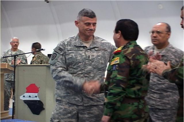 Maj. Gen. Caslen shakes hands with Brig. Gen. Khadir as onlookers applaud the signing of the SOI contract.